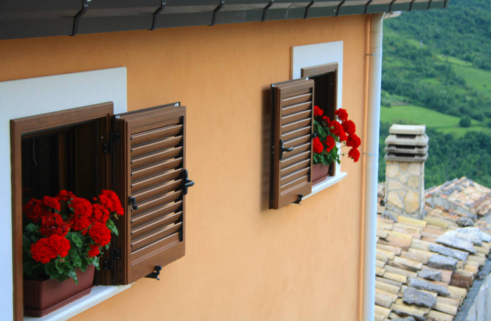 Vibrant red carnations on window sills in Caramanico Terme in Abruzzo, Italy
